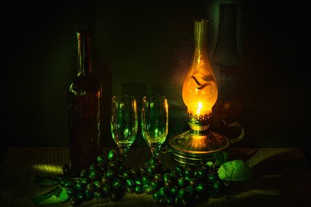 a bottle of red wine and two glasses against a background of black grapes in the dim light from a kerosene lamp Zdjęcie Seryjne