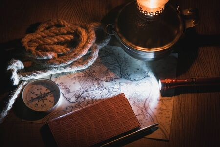 planning a trip at night at a table in the light of a kerosene lamp. Researching an old map with a compass and writing to notebook Zdjęcie Seryjne