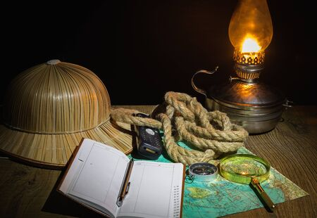 Preparing for an adventure trip. At night, inspection of an old map with a compass and a magnifier under the light of a lamp. Dark background.