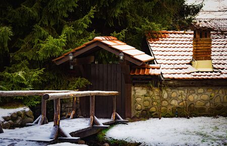 rustic winter landscape. entrance to the courtyard of an old house with a tiled roof with a brick pipe Фото со стока