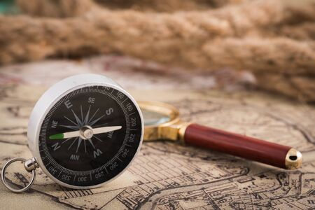 compass and magnifying glass lie on the topographic map Imagens