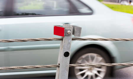 Barrier guard on the road pole with a tensioned cable between the oncoming lanes of the car for safety Imagens