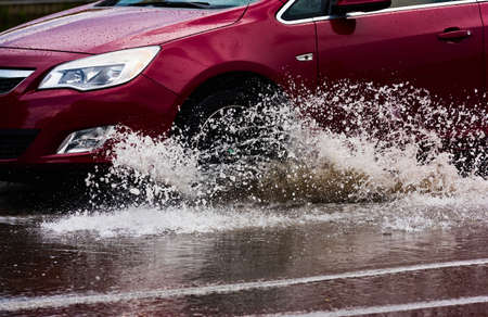 motion car rain big puddle of water spray from the wheels Archivio Fotografico