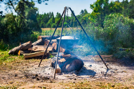 a camping cooking pot hanging over a campfire on a tripod at a tourist camp Foto de archivo
