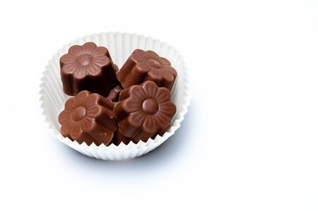 Daisy shaped chocholate assortments in a paper basket isolated on white