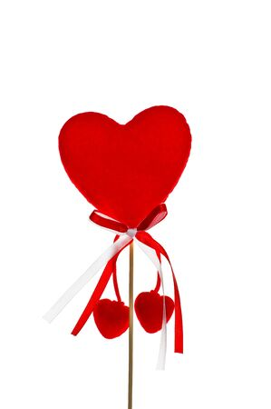 A big red heart on a wooden stick with a tie and two hanging little hearts isolated on white photo