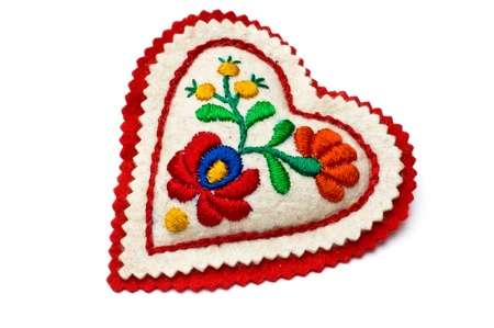Heart shaped needle pillow decorated with Hungarian embrodiery isolated on white Stock Photo