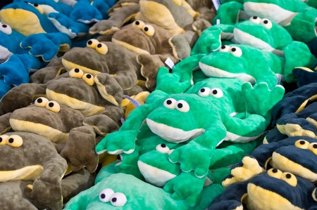 Background of piled toy frogs front view