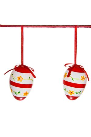 Two easter eggs hanging on a red line isolated on white photo