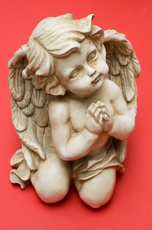 Praying angel looking sideways isolated on red Stock Photo - 10848208