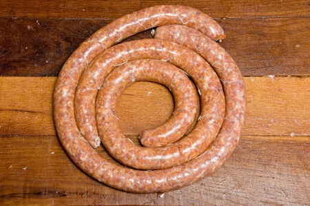 Two spiralled spicy raw sausages on wooden table Stock Photo - 10848232