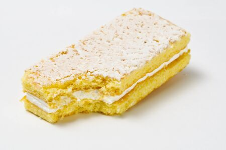skimming: Lifted sponge cookie with skimming filling bite isolated on gray