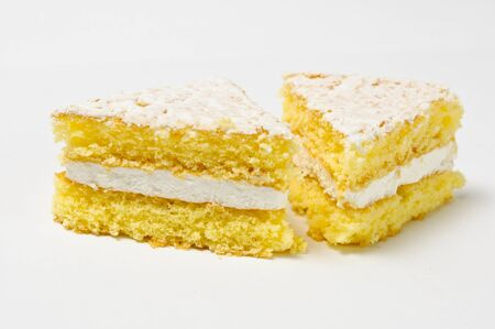 skimming: Side view of two triangles of sponge cookies with skimming filling isolated on gray
