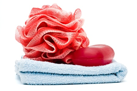 Bath rose and soap bar on top of blue towel isolated on white
