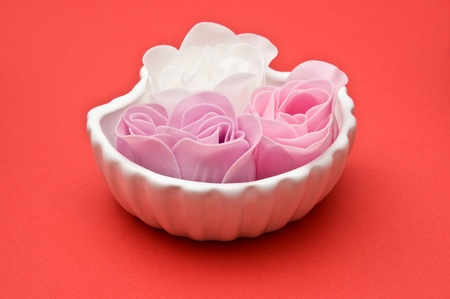 Clay shell holder of soap roses on red background