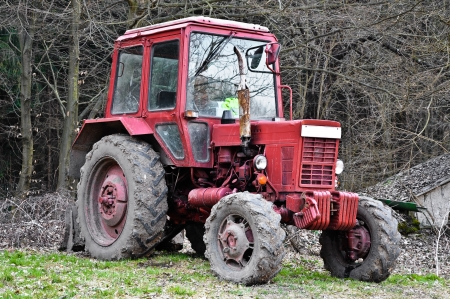 Dirty red tractor in the woods Stock Photo - 14484800