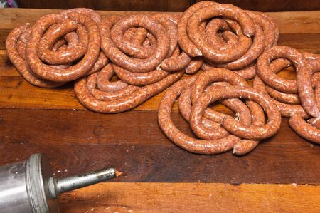 Freshly made raw sausages piled on wooden table