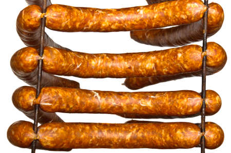 Four sausages ready to smoke on drying rods isolated on white Stock Photo