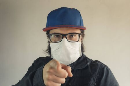 Man in a blue cap pointing at you wearing a white face mask to protect from dust and coronavirus