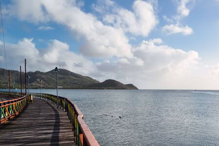 A beautiful shot of a boardwalk in the sea with a mountain and a cloudy blue sky in the background Stock Photo