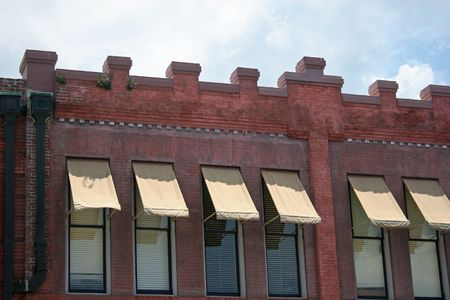 awnings: Old brick wall and windows with awnings