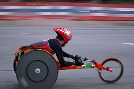 razas de personas: Competidor en la carrera de sillas de ruedas de carretera  Foto de archivo