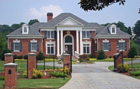 Large brick house behind iron gate Stock Photo
