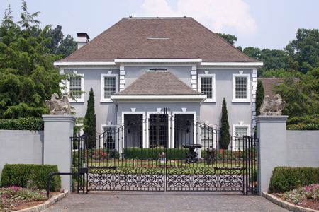 Large stucco house behind iron gate