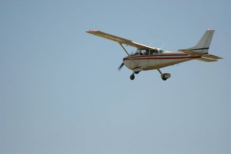 Small plane airborne against sky