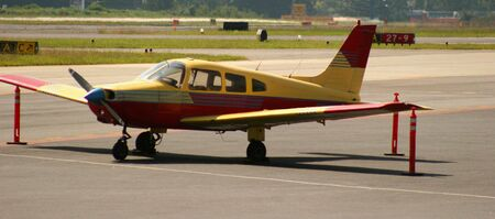 Red and Yellow airplane on tarmac Stock Photo