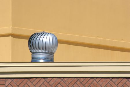 Aluminum roof vent on top of stucco building