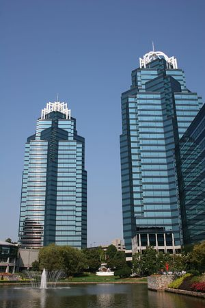 Twin blue office towers by lake against blue sky