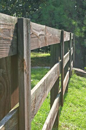 Old wooden slat rail fence outside horse pasture Stock Photo - 561460