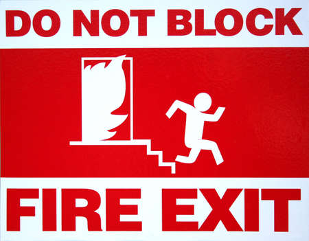 Red and white fire exit sign in commercial building