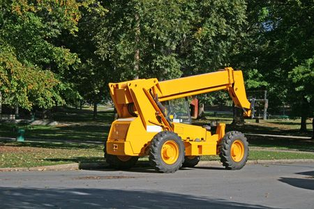 industrial park: Yellow industrial forklift outside in park setting Stock Photo