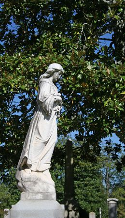 Old statue on top of tombstone in cemetery Stock Photo - 589444