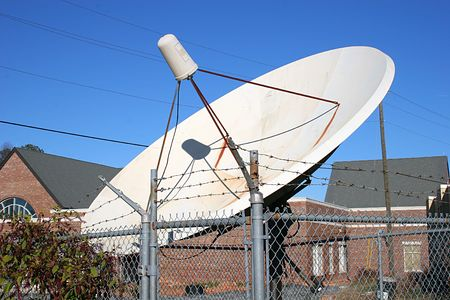 An Old satellite dish in fenced enclosure photo