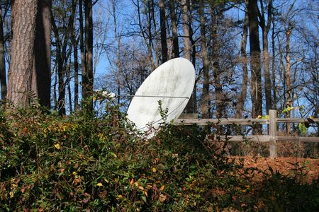 A satellite dish in a woodland environment Stock Photo - 658693