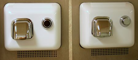 A pair of electric hand dryers in a restroom