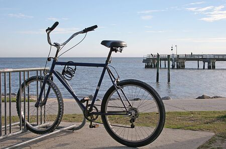 Solitary bike captured against backdrop of beach and pier photo
