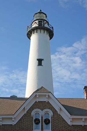 A Lighthouse behind roofline decorated for Christmas photo