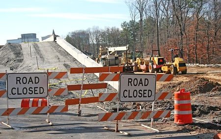 Road and bridge construction site with road closed signs and heavy equipment photo