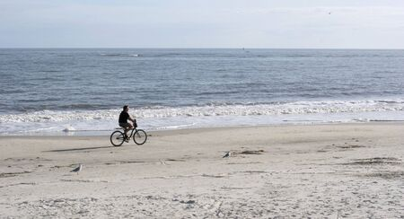A Lone bicycle rider on a winter beach photo