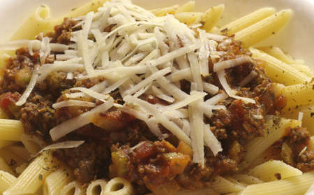 A serving of penne pasta with meat sauce photo