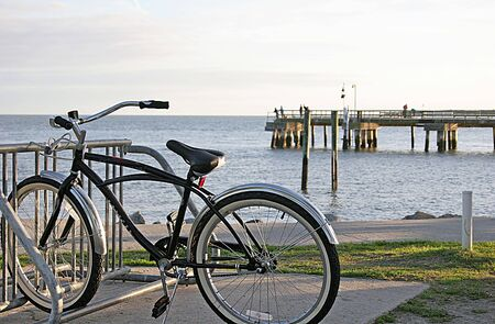 A lone bicycle in rack in front of pier at the beach Stock Photo - 720474