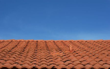 Red Clay tile roof against blue sky photo