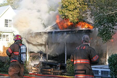 Two fireman working a flaming smoking house fire photo