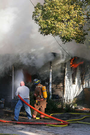 house on fire: Civilian volunteer assisting fireman in putting out house fire