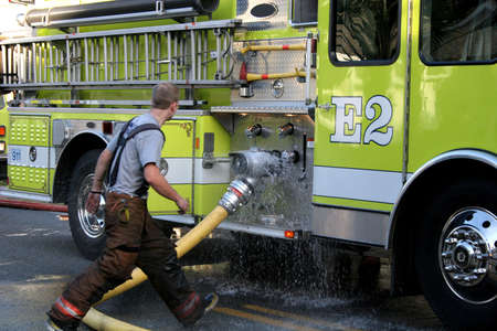 Fireman attaching leaky hose to firetruck at scene