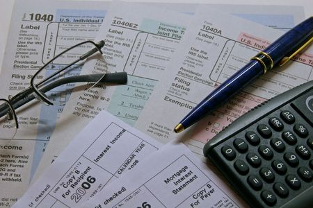 U.S. tax forms with glasses, pen, and calculator photo
